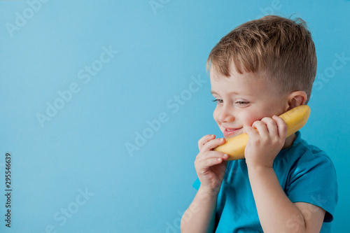 Little Boy tries to speak by means of a banana instead of phone. фототапет