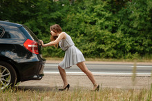 Woman Pushing Broken Car On Ro...
