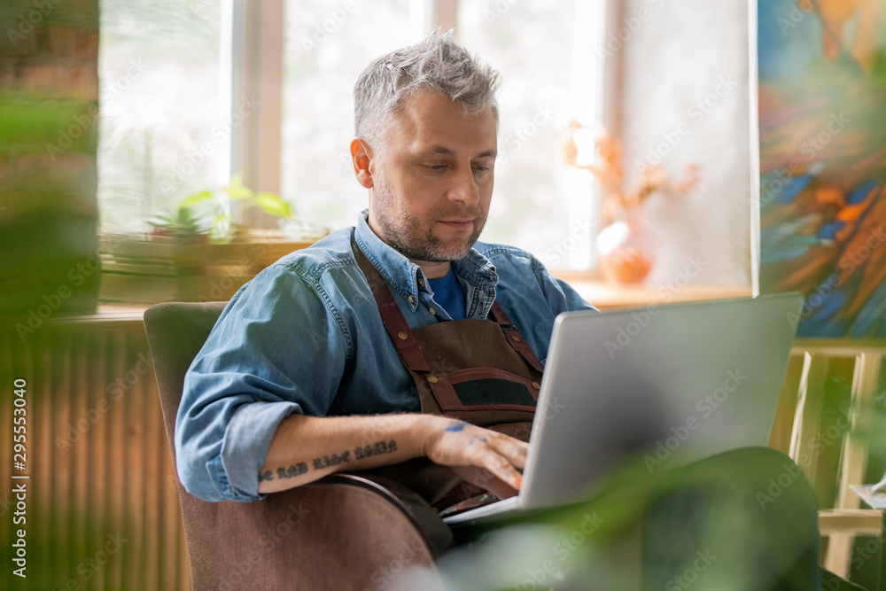 Fototapety, obrazy: Serious painter in workwear sitting in studio in front of laptop display