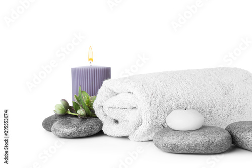 Composition with spa stones, towel and candles isolated on white