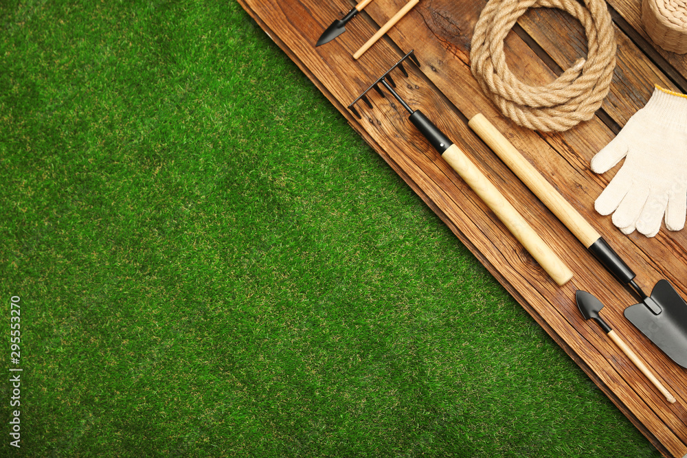 Fototapety, obrazy: Wooden surface with gardening tools on green grass, flat lay. Space for text
