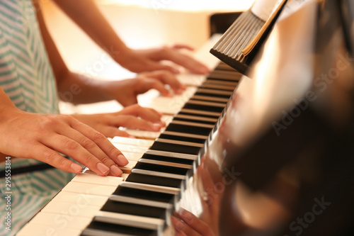 Young woman teaching little girl to play piano indoors, closeup - 295553814