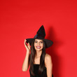 canvas print picture - Beautiful young woman wearing witch costume for Halloween party on red background, space for text