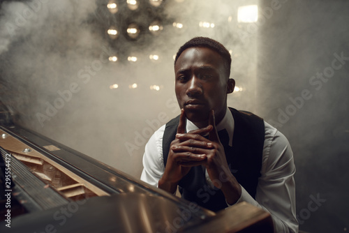 Ebony grand piano musician poses on the stage - 295554472