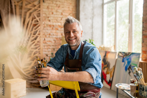 Pinturas sobre lienzo  Cheerful artist in workwear sitting on chair in front of camera