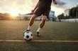 Leinwandbild Motiv Male football player hits the ball on the field