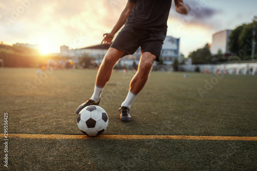 Male football player hits the ball on the field