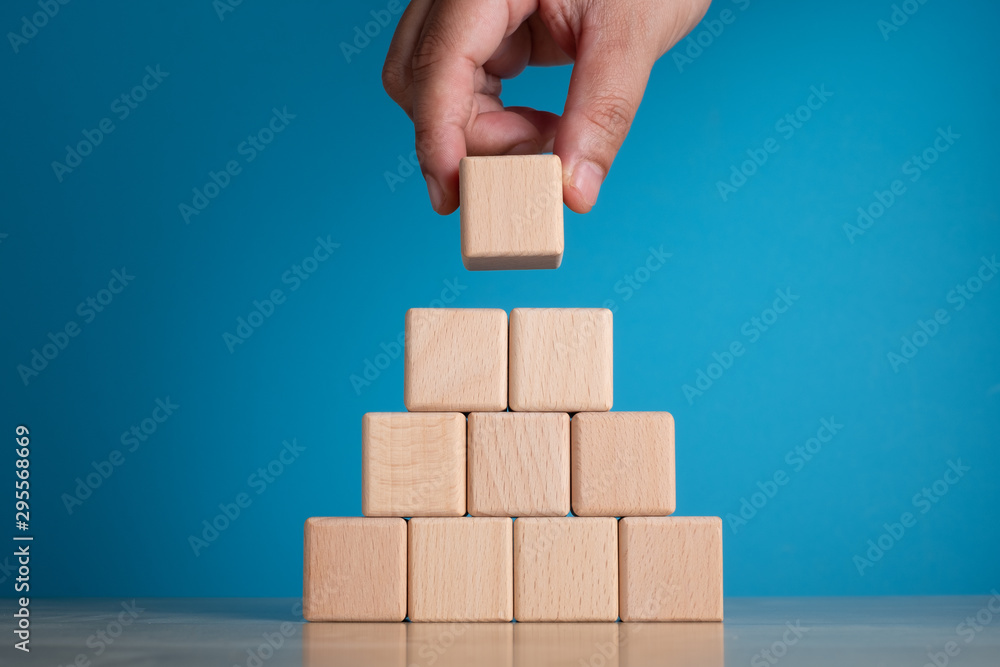 Fototapety, obrazy: Hand arranging block on blue background. Business concept on progress or building something.