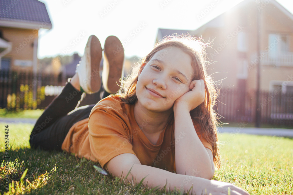 Fototapety, obrazy: Portrait of smiling teen girl lying on sunny green grass of cottage village on background