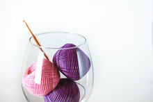 Eco-friendly Cotton Yarn. Skeins Of Purple And Pink Yarn In A Glass Goblet. Items For Female Needlework On A White Wooden Table. Hook For Luck. Space For Your Text.