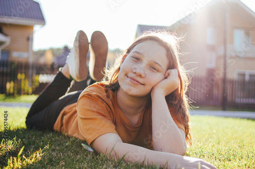 Portrait of smiling teen girl lying on sunny green grass of cottage village on b Fototapete