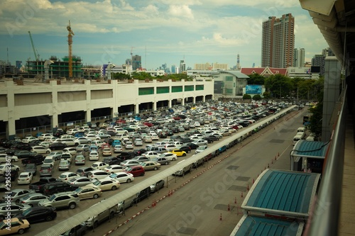 Fototapety, obrazy: Wide shot of vehicles parked in a parking lot near a building under construction