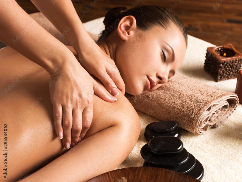 Fototapeta Beautiful woman relaxing with back massage at spa salon.