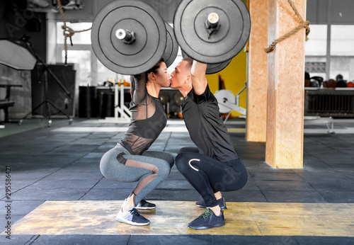 Fotografía Fitness couple making a Barbell Jerk and kissing each other