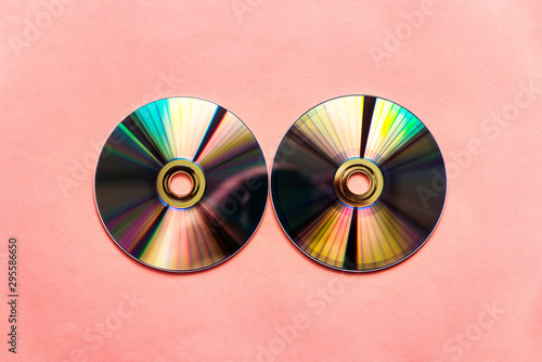 Light reflected compact discs on pink paper background. - 295586650
