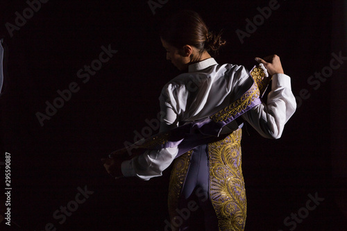 Woman bullfighter by dressing with vest on your back on a black background