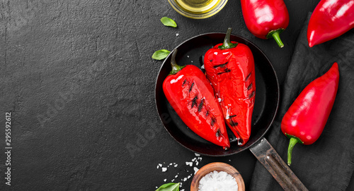 Fotomural  Grilled red pepper in grilling pan on black background.
