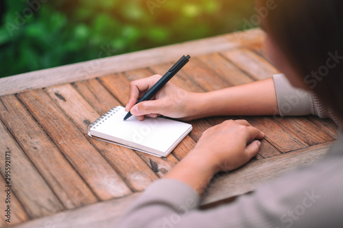 Closeup image of a woman writing on blank notebook on wooden table in the outdoors