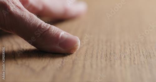 Obraz man hand touch oil finished oak wood surface - fototapety do salonu