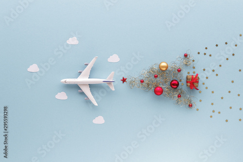 Christmas composition. Airplane flying in sky star gift bauble top view background with copy space for your text. Flat lay