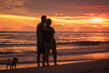 Happy Couple Hugging On The Beach In Colorful Sunset With Dog