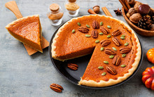 Festive Homemade Pumpkin Pie Decorated With Pecan Nuts And Pumpkin Seeds.