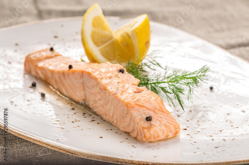 Steamed salmon with lemon on white plate on grey tablecloth Poster Mural XXL