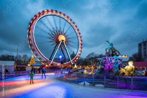 Christmas market near the Neptune Fountain in Berlin with Ferris wheel and ice rink in winter - 295598278