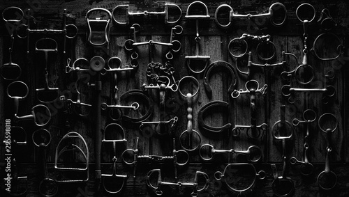 Photo top down photo of horse equipment, bits & shoes on a wooden table in black & white
