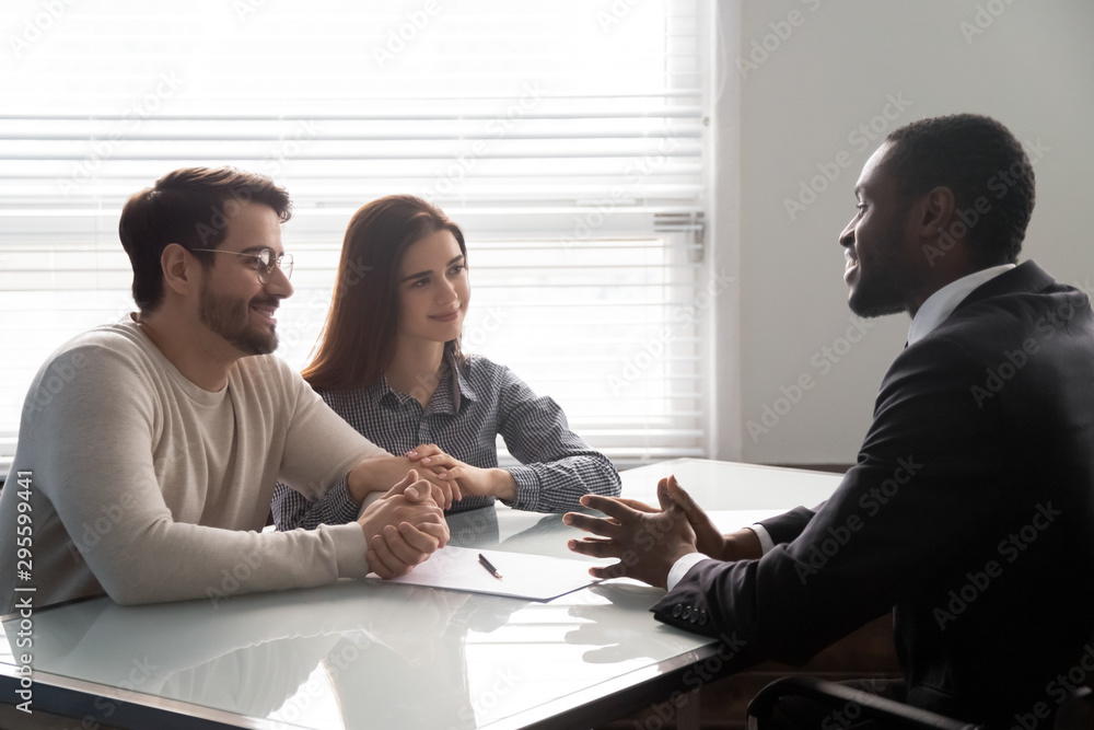 Fototapeta Smiling african american male banker consulting young married couple.