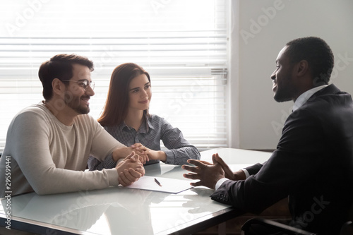 Fotomural  Smiling african american male banker consulting young married couple