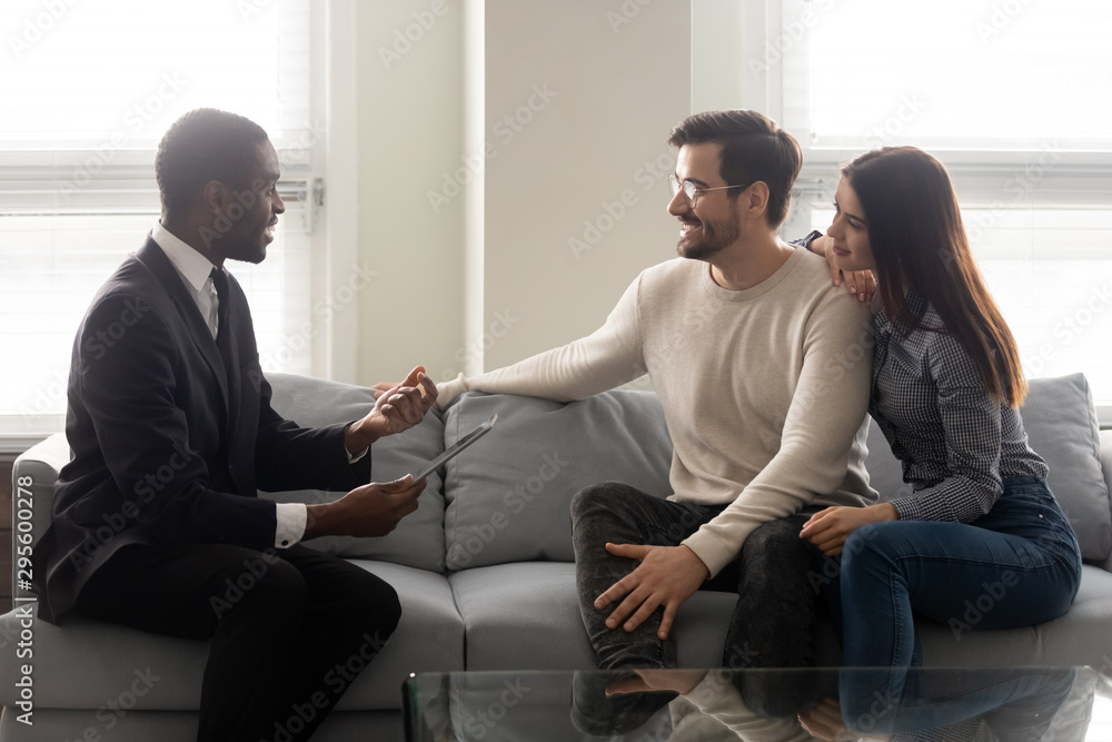 Fototapeta Happy young family couple listening to financial expert offer.