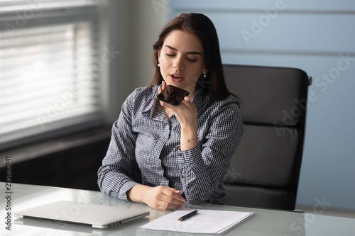 Photo Friendly businesswoman recording voice message on smartphone.