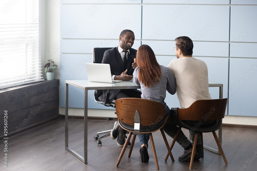 Fototapeta Happy smiling african american male realtor consulting young married couple.