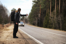 A Young Man Is Hitchhiking Around The Country. The Man Is Trying To Catch A Passing Car For Traveling. The Man With The Backpack Went Hitchhiking To The South.