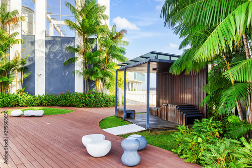 Beautiful rooftop garden. Modern wooden arbor among green trees Fototapete
