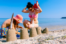 Child Girl In Summer Hat Is With Her Mom At The Beach Sculpting Sand Castles