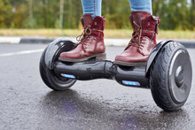 Close Up Of Woman Using Hoverboard On Asphalt Road. Feet On Electrical Scooter Outdoor