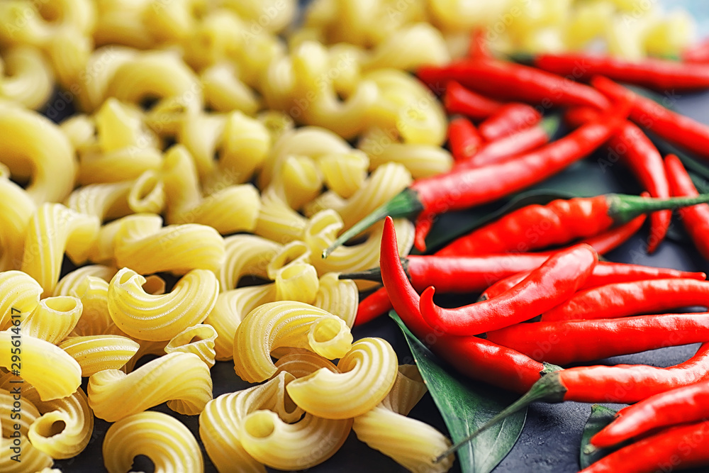 Fototapety, obrazy: Uncooked pasta on a stone background. With seasonings and spices, spicy chili peppers.