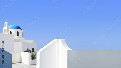 Santorini blue dome and whitewashed structures on light blue sky