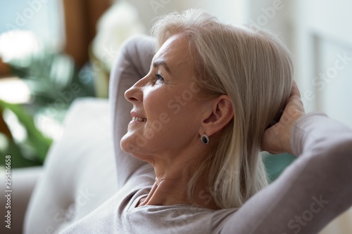 60s woman put hands behind head resting indoors enjoy weekend