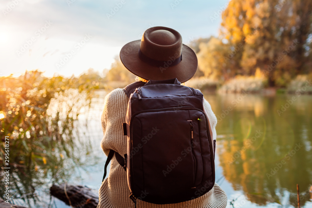 Fototapeta Tourist with backpack sitting on river bank at sunset. Middle-aged woman relaxing and admiring autumn nature