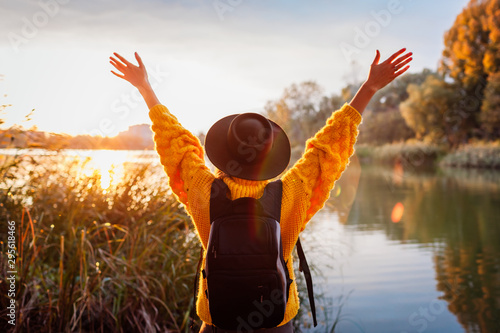 Fototapeta Traveler with backpack relaxing by autumn river at sunset. Young woman raised arms feeling free and happy obraz
