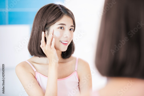 Fototapeta  woman apply cream on face