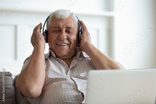Senior man wearing headphones listens songs on laptop - 295619229