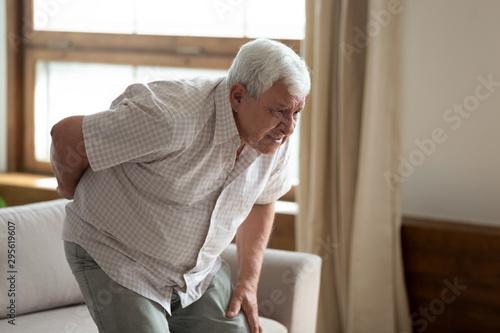 Fotografía Senior man got up from couch felt low back pain