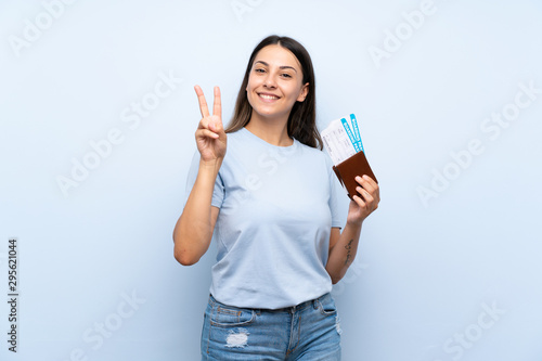 Pinturas sobre lienzo  Traveler woman with boarding pass over isolated blue wall smiling and showing vi