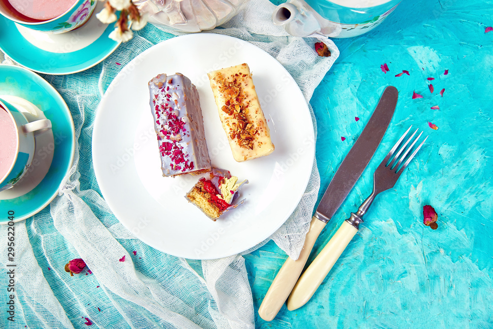 Fototapety, obrazy: Mini Mousse Cake with chocolate, covered with blue spray and decorated with pink roses with cups of tea on blue background.