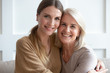 canvas print picture - Attractive aged mother and adult daughter hugging looking at camera