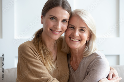 Fototapeta Attractive aged mother and adult daughter hugging looking at camera obraz